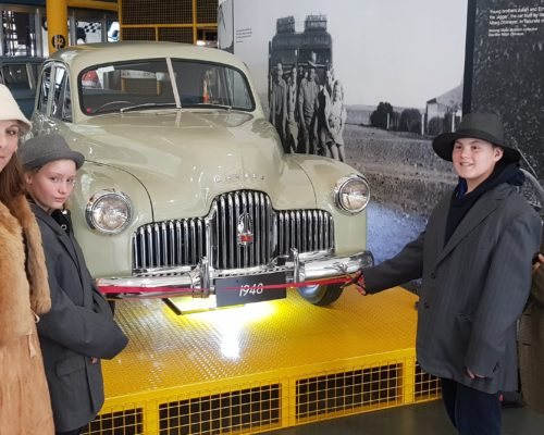 students in costume cutting ribbon of the first holden produced